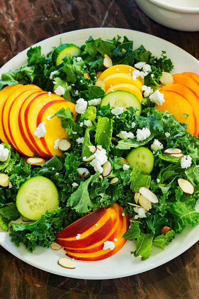 This peach goat cheese kale salad showcases ripe peaches, tangy goat cheese and crunchy almonds with a delicious balsamic vinegar dressing.
