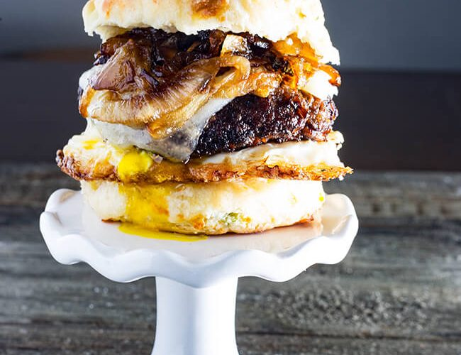 This Cheddar Steak Egg & Cheese Biscuit Sandwich is the perfect breakfast sandwich to start your day or the perfect breakfast for dinner option. A mouthwatering country-fried steak on a freshly baked, scratch-made biscuit topped with a crispy fried runny egg and spicy caramelized onion.